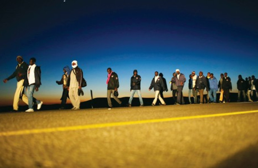African migrants walk on a road in December 2013 after choosing to leave the Holot open detention facility (photo credit: REUTERS)