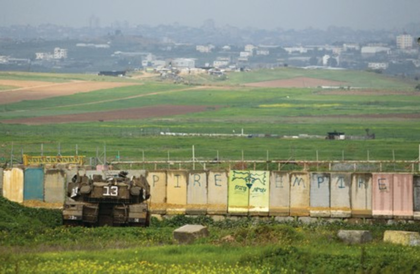 An IDF tank positions itself outside the border of the northern Gaza Strip in this photo from March 2014 (photo credit: REUTERS)