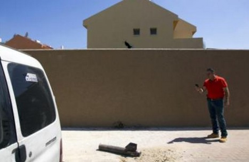 A neutralised Gaza rocket displayed by police after it landed in a house (back) in  Sderot July 3, 2014. (photo credit: REUTERS)