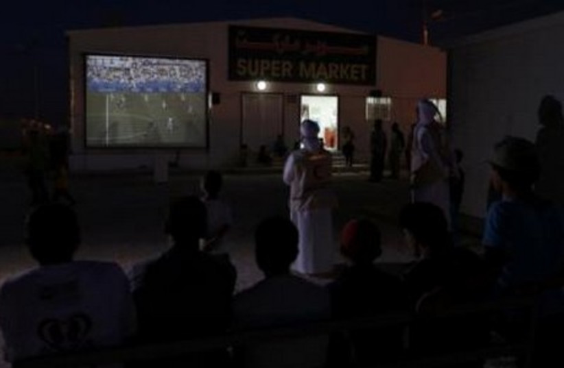 UAE Red Crescent members and Syrian refugees gather round a large screen to watch a World Cup soccer match.  (photo credit: REUTERS)