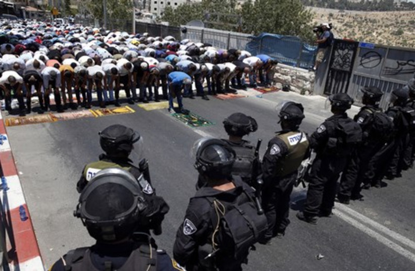 Palestinians pray on the first Friday of Ramadan in the Wadi al-Joz section of east Jerusalem. (photo credit: REUTERS)
