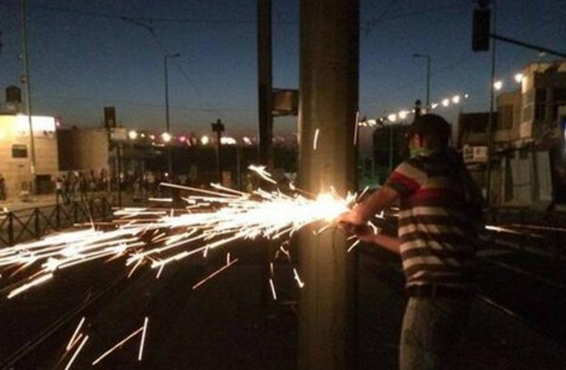 Palestinian taking a disk-saw to an electricity pole in Jerusalem, July 4, 2014.  (photo credit: ISRAEL POLICE)