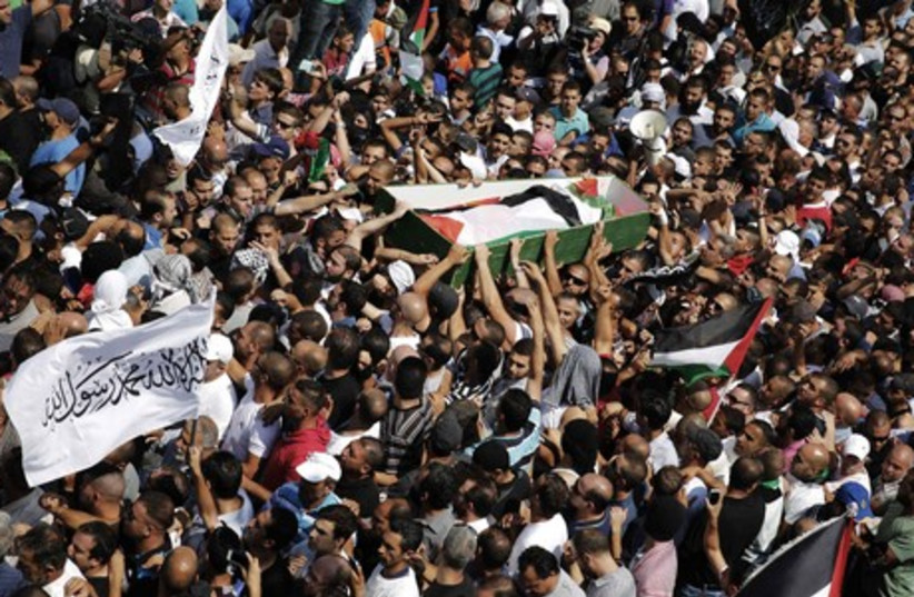 Palestinians carry the body of Mohammed Abu Khdeir during his funeral in Shuafat (photo credit: REUTERS)