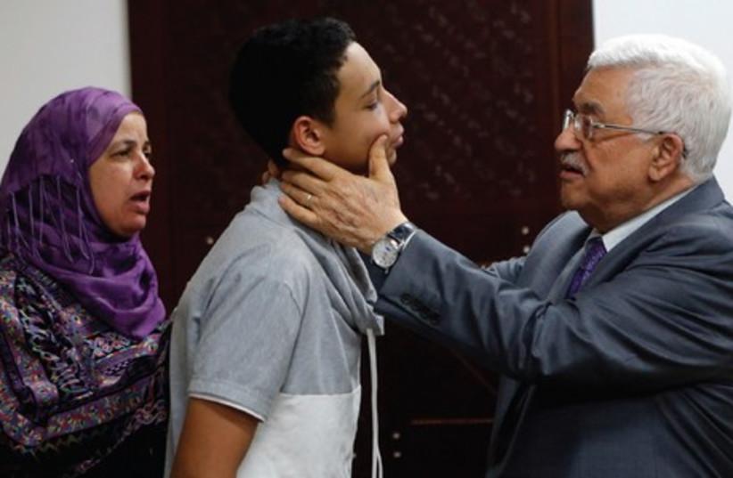 PA PRESIDENT Mahmoud Abbas examines the face of Tariq Abu Khdeir in Ramallah yesterday. (photo credit: REUTERS)