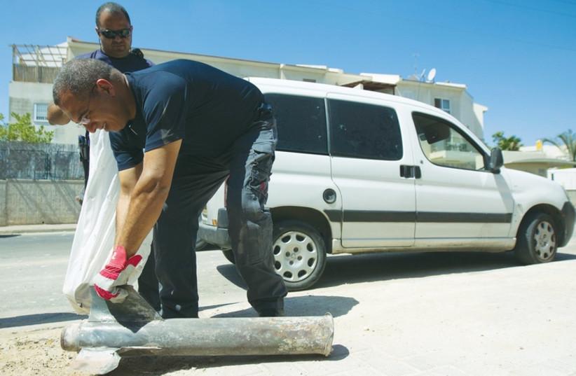 A man picks up a Kassam rocket after it landed in Sderot on July 3 (photo credit: REUTERS)