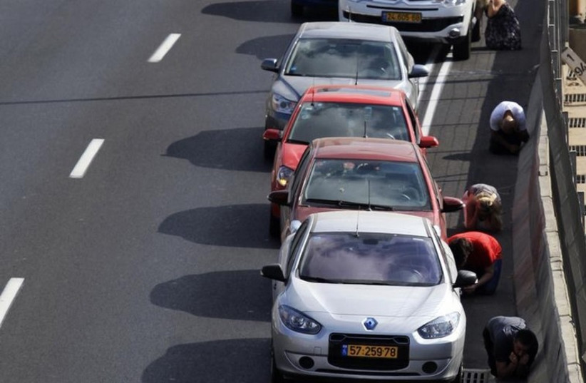 Drivers take cover as sirens sounds in Tel Aviv  (photo credit: REUTERS)