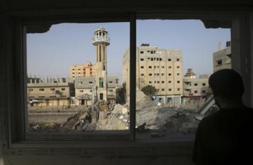 A Palestinian man looks through a broken window in the Gaza Strip, which police said was destroyed in an IAF strike. (photo credit: REUTERS)