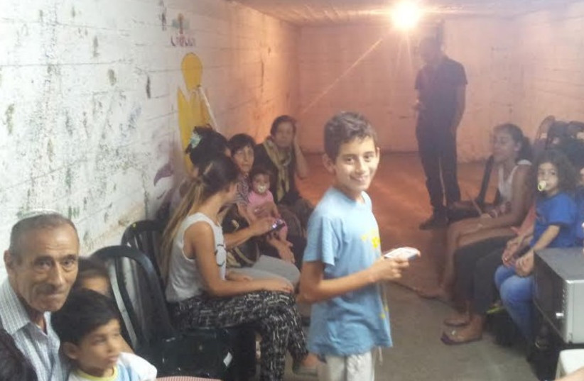 People stand in bomb shelter in Tel Aviv during rocket siren (photo credit: Courtesy)