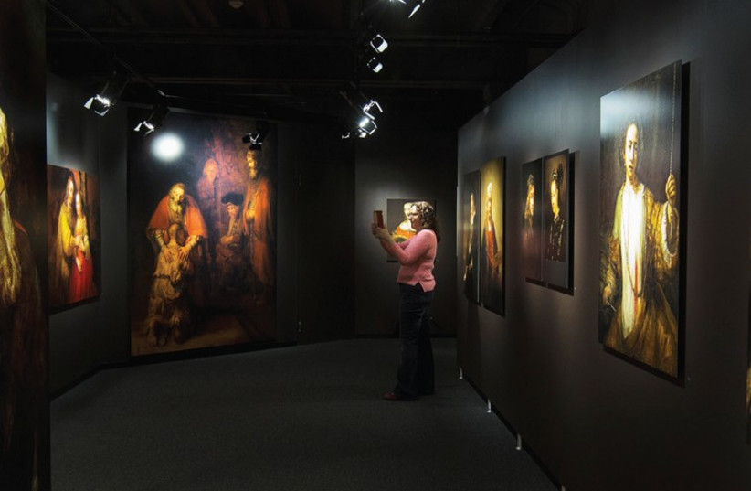 A TOURIST takes a picture of one of the reproductions by the Dutch painter Rembrandt van Rijn at Magna Plaza shopping center in Amsterdam. (photo credit: REUTERS)