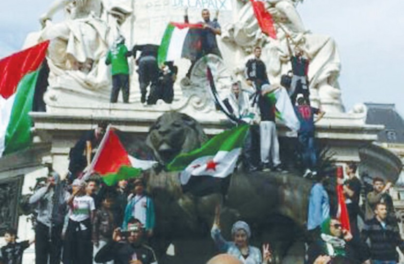 ANTI-ISRAEL PROTESTERS display Palestinian flags at the Place de la Bastille in Paris. (photo credit: DAVID YAEL)