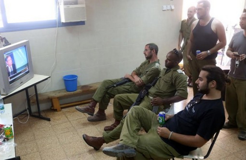 IDF RESERVISTS watch television in a Kiryat Gat community center as they wait for orders. (photo credit: MARC ISRAEL SELLEM/THE JERUSALEM POST)