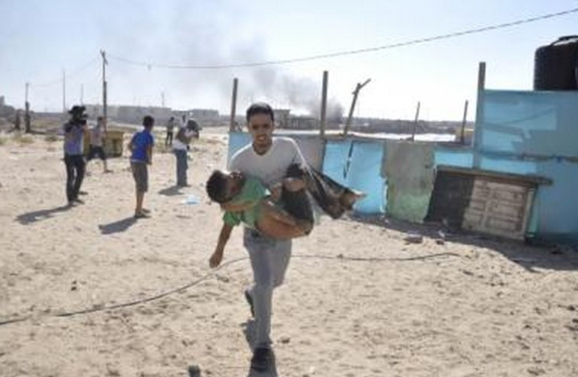 Man carries child on Gaza beach after Navy shelling (photo credit: REUTERS)