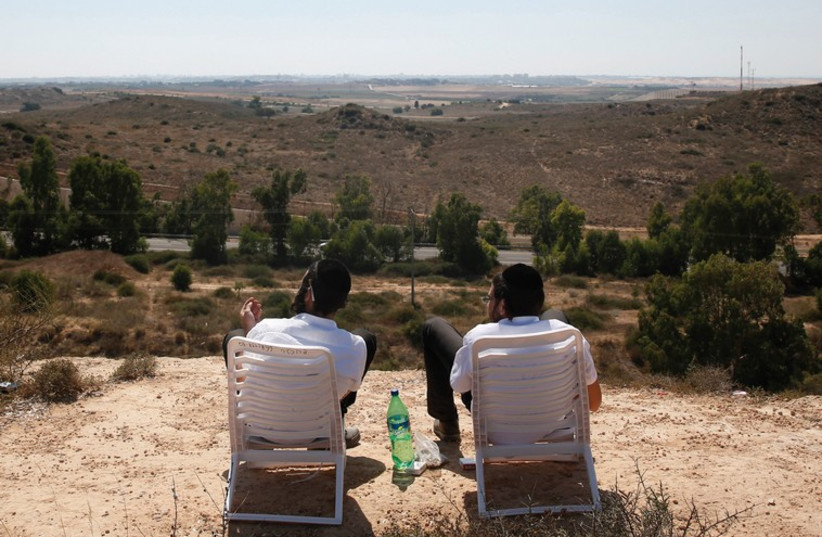 Two students watch the bombardment of Gaza on July 10. (photo credit: REUTERS)