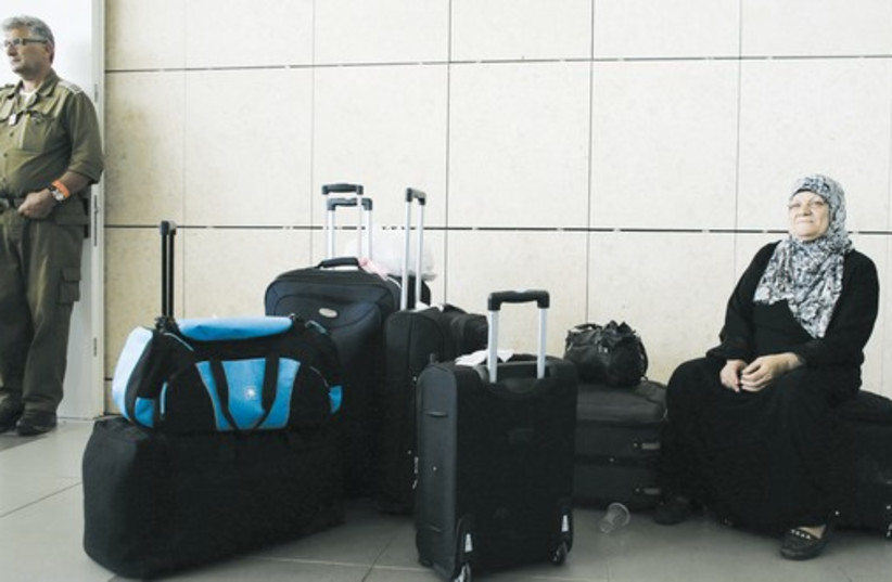A palestinian woman sits on a suitcase at Israel's Erez Crossing after leaving Gaza on Sunday. (photo credit: REUTERS)