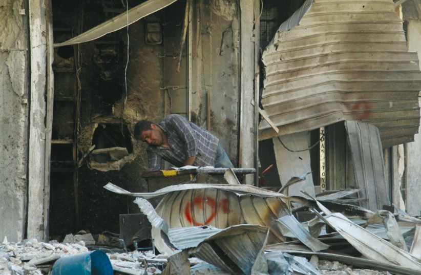 A site hit by what activists said was shelling by forces loyal to Syria's President Bashar Assad in the al-Myassar neighborhood of Aleppo this week. (photo credit: REUTERS)