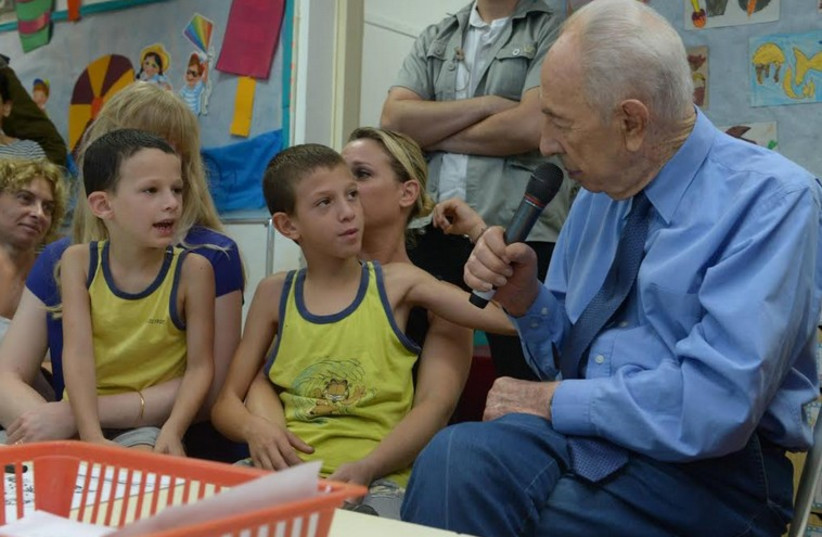Former president Shimon Peres speaking with children and parents at Kibbutz Zikim. (photo credit: GPO)