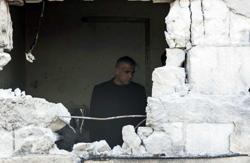 Israeli Finance Minister Yair Lapid stands in a house damaged by a rocket, fired by Palestinian militants, that landed in the southern town of Sderot (photo credit: REUTERS)
