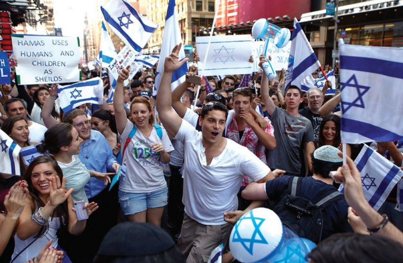 SUPPORTERS OF ISRAEL dance during a rally in New York on Sunday. (photo credit: REUTERS)