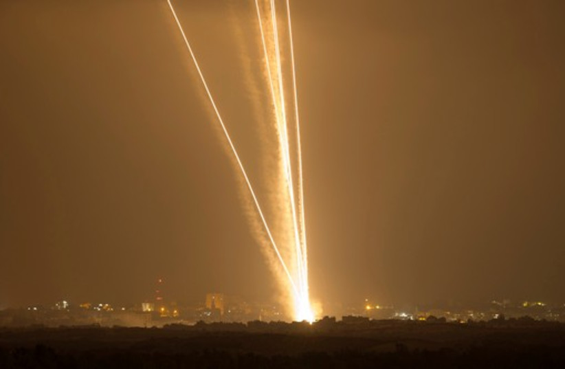 Light streaks and smoke trails are seen as rockets are launched from Gaza towards Israel July 23, 2014 (photo credit: REUTERS)