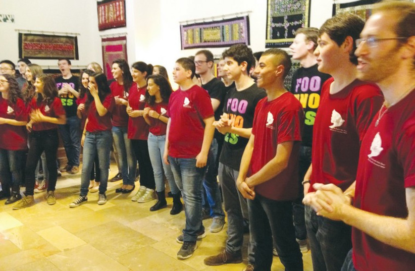 A joint Israeli and Palestinian youth choir at the YMCA sing together in an effort to build coexistence. (photo credit: BRIAN BLUM)