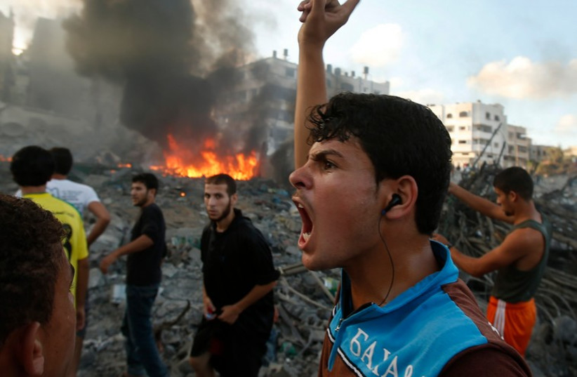 A Palestinian reacts following what witnesses said was an Israeli air strike on a building in Gaza City July 24, 2014. (photo credit: REUTERS)