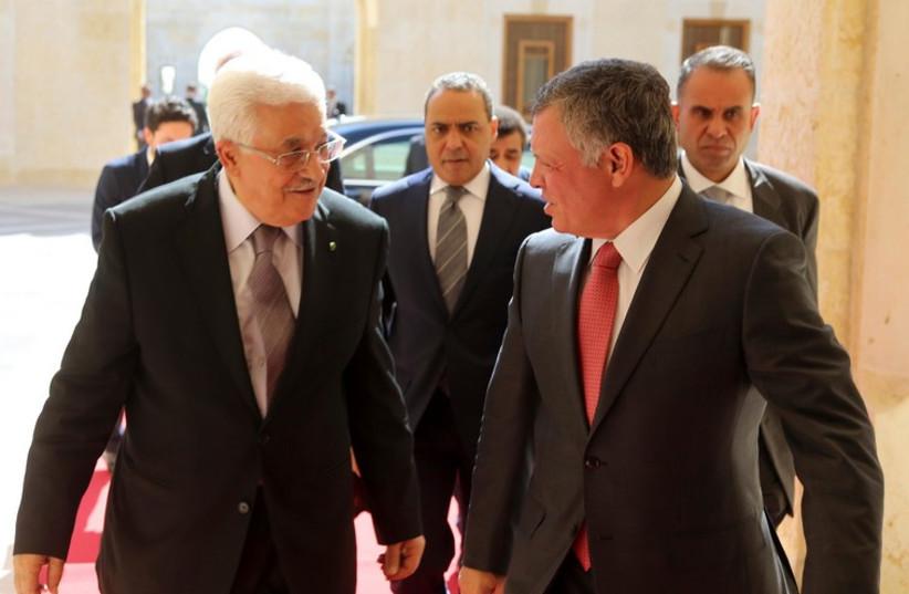 Jordan's King Abdullah (R) welcomes Palestinian President Mahmoud Abbas at the Royal Palace in Amman (photo credit: REUTERS)