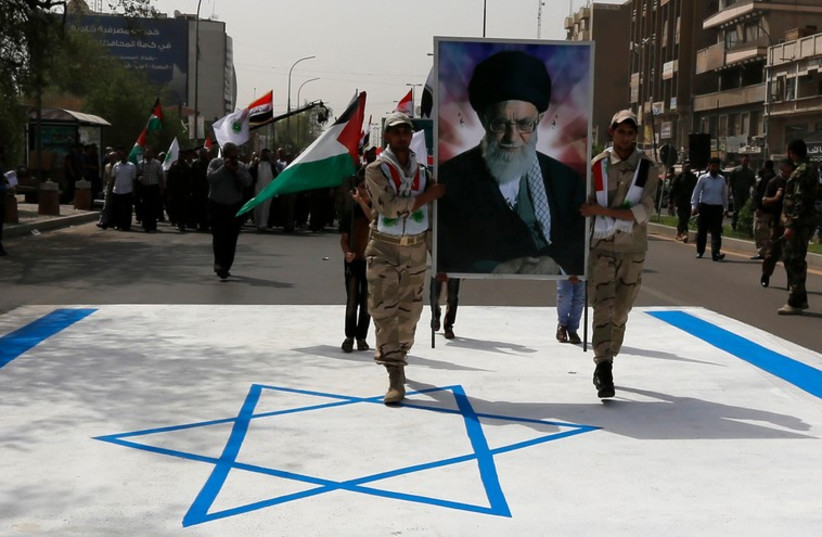 Iraqi muslims from Shi'ite Badr organization hold a portrait of Ayatollah Ali Khamenei as they walk over the Israeli flag during a parade marking Jerusalem Day. (photo credit: REUTERS)