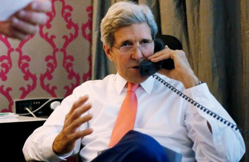 US Secretary of State John Kerry speaks on the phone to Prime Minister Binymain Netanyahu, from his hotel suite in Cairo July 25, 2014.  (photo credit: REBECCA FRIEDMAN)