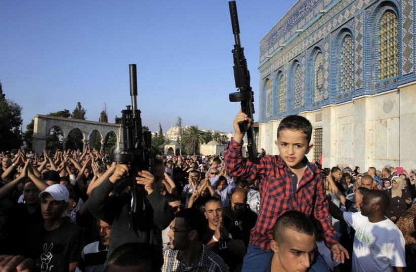 Palestinian children hold toy guns during a protest in Jerusalem (photo credit: REUTERS)