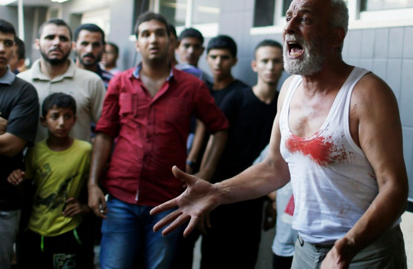The father of a Palestinian boy reacts following his death at a hospital in Gaza City July 28, 2014. (photo credit: REBECCA FRIEDMAN)