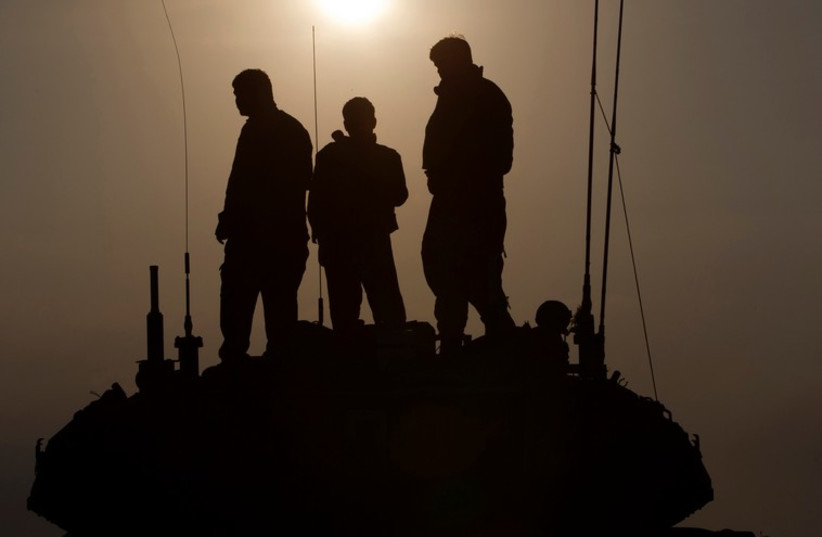 IDF soldiers stand atop a tank near the border with Gaza. [File] (photo credit: REUTERS)