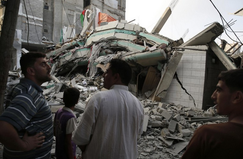 Palestinians stand by the rubble of the home of Hamas Gaza leader Ismail Haniyeh in Gaza City (photo credit: REUTERS)