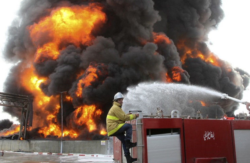 A Palestinian firefighter works during efforts to extinguish a fire at Gaza's main power plant. (photo credit: REUTERS)