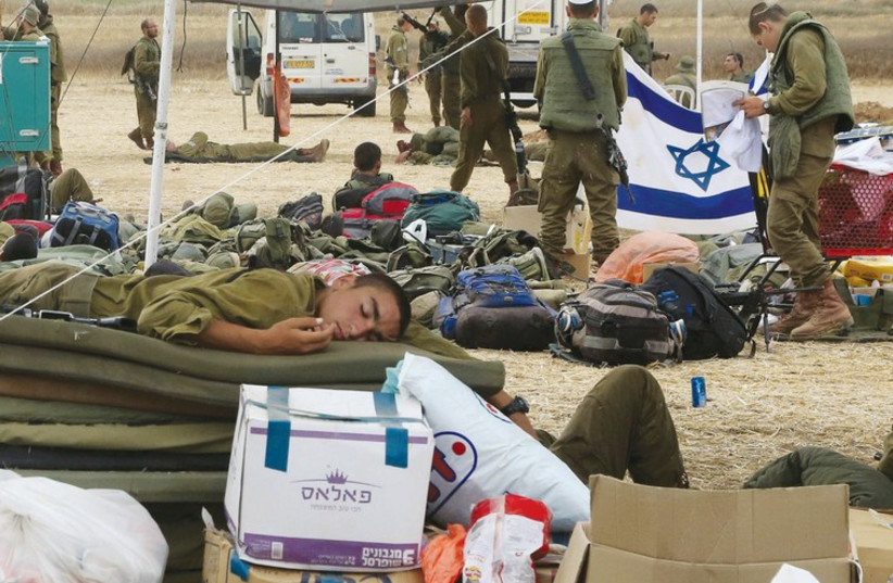 A soldier sleeps at a base camp near the border with the Gaza Strip, surrounded by packages donated by citizens. (photo credit: MARC ISRAEL SELLEM/THE JERUSALEM POST)