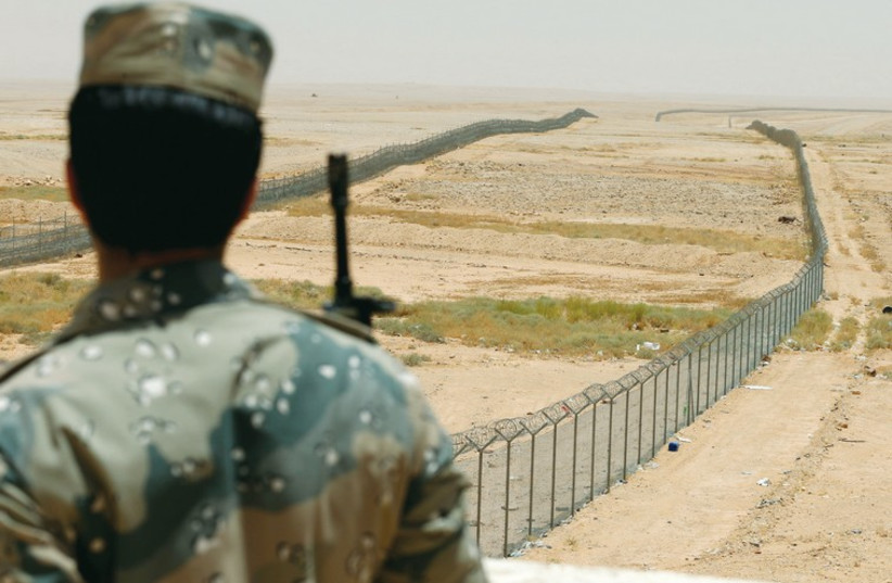 A member of the Saudi border guards force stands guard next to a fence on Saudi Arabia's northern borderline with Iraq last month. (photo credit: REUTERS)