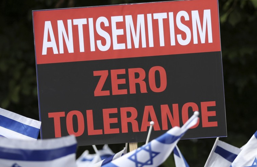 Demonstrators hold a placard and wave Israeli flags during a rally in support of the Israeli offensive on the Gaza Strip (photo credit: REUTERS)