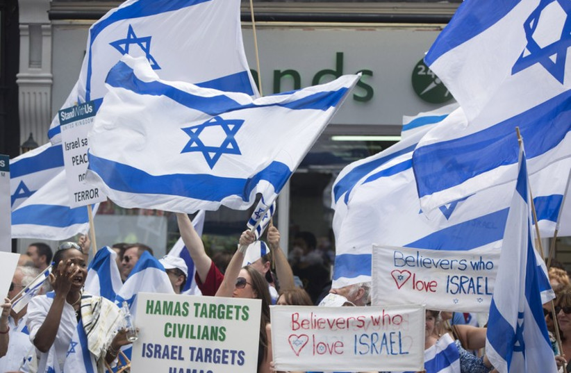 Demonstrators hold signs and Israeli flags during a rally outside Israel's Embassy in London, to show support for Israel's military action in Gaza (photo credit: REUTERS)