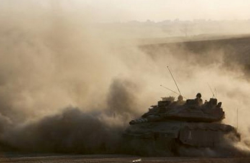 An Israeli tank drives near the border as it returns to Israel from Gaza. (photo credit: REUTERS)