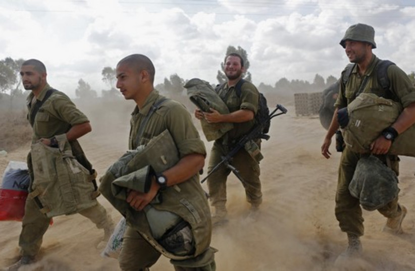 Israeli soldiers arrive at a staging area near the border with Gaza Strip (photo credit: REUTERS)