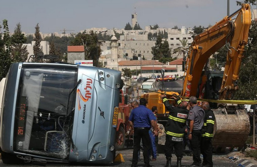 Bus flipped by tractor in Jerusalem terror attack (photo credit: MARC ISRAEL SELLEM/THE JERUSALEM POST)