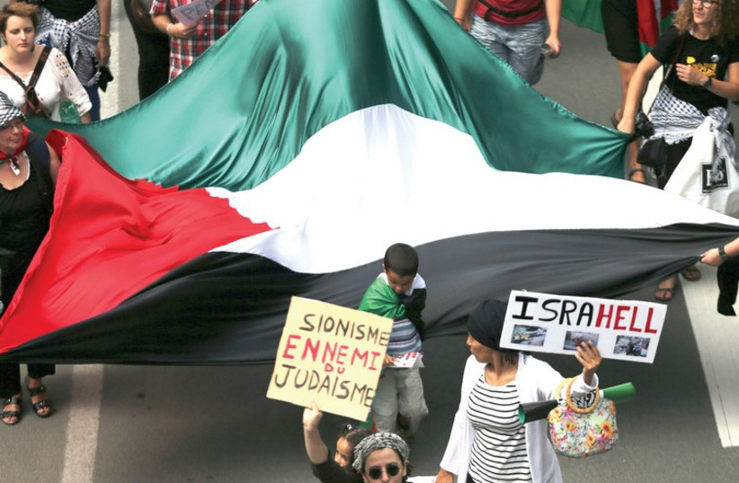 Demonstrators in Brussels hold a giant Palestinian flag and anti-Israel signs (photo credit: REUTERS/FRANCOIS LENOIR)