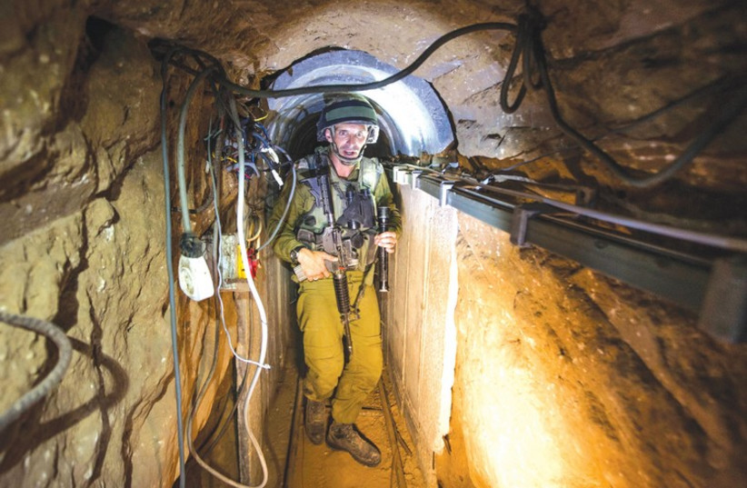 An IDF soldier traverses a tunnel used by Hamas gunmen for cross-border attacks (photo credit: REUTERS)