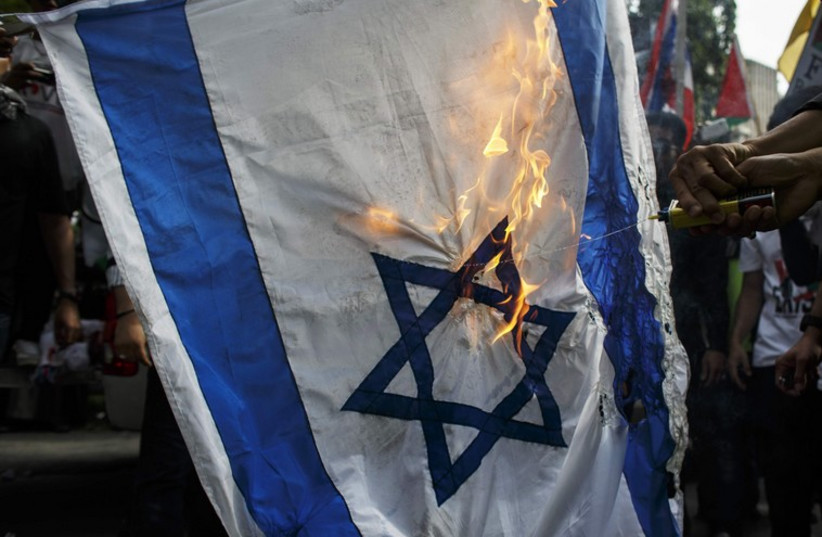 Demonstrators burn an Israeli national flag during an anti-Israel protest (photo credit: REUTERS)