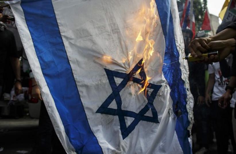 Demonstrators burn an Israeli national flag during an anti-Israel protest (photo credit: REUTERS)