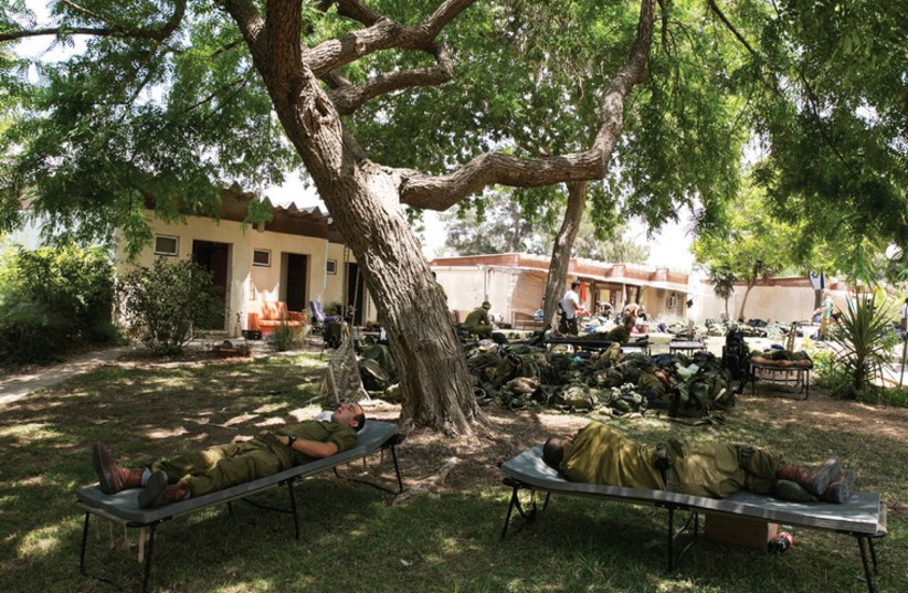 Soldier camp out last month on the lawn in Kibbutz Nir Am, just outside the Gaza Strip. (photo credit: REUTERS)