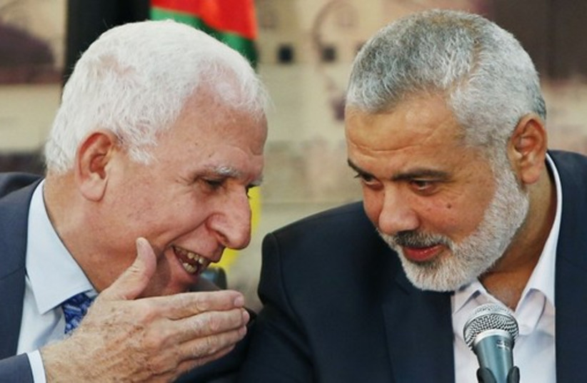 Fatah official Azzam al-Ahmad (L) and Hamas leader Ismail Haniyeh. (photo credit: REUTERS)