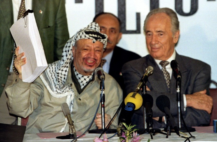 PLO chairman Yasser Arafat holds the second phase of the Oslo peace accords after the initialling of the document, September 24. (photo credit: REUTERS)