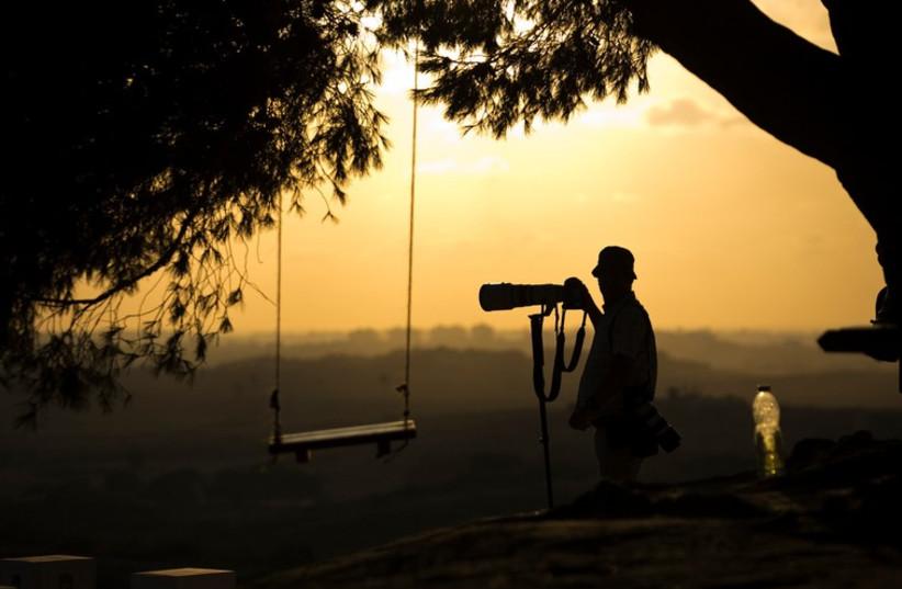 Cameraman takes photo (illustrative) (photo credit: REUTERS)