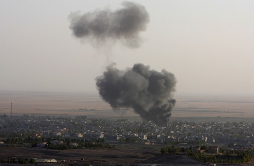 Smoke billows from the town of Makhmur during clashes between Iraqi Kurdish Peshmerga troops and Islamic State (IS) militants. (photo credit: REUTERS)