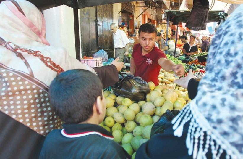 Palestinian shop at a market in Gaza City. (photo credit: REUTERS)